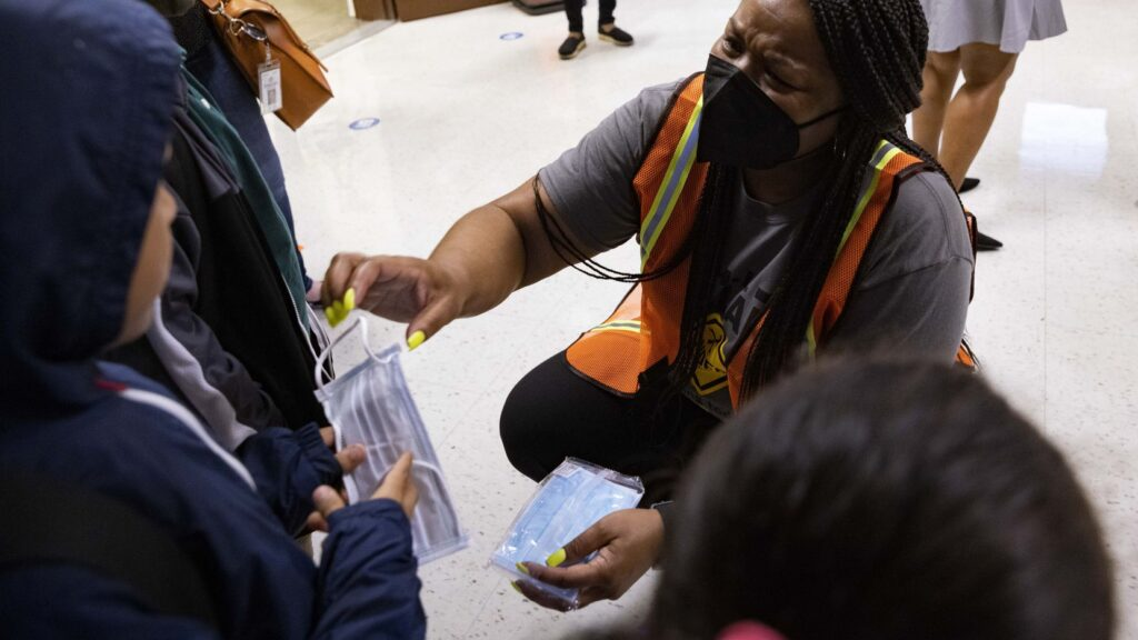 Principal Shanieka Christmas-McDonald hands out masks during the first day of school on Monday, Aug. 2, 2021, at H.I. Holland Elementary School in Dallas.