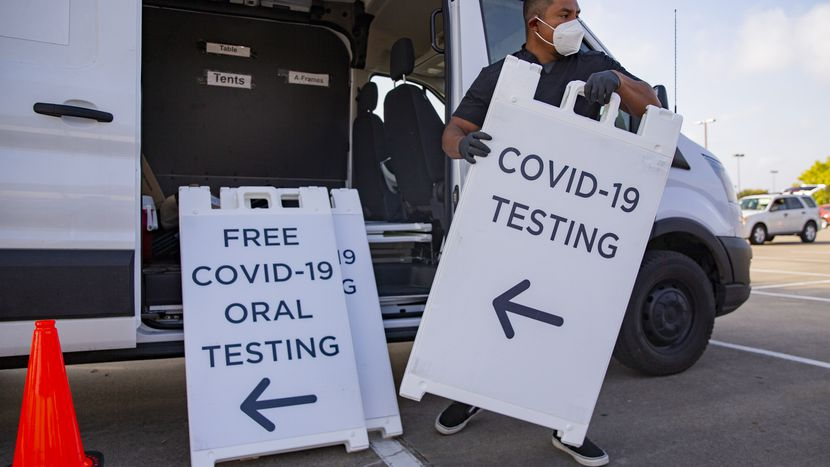 Medical assistant unloading signs for covid-19 testing